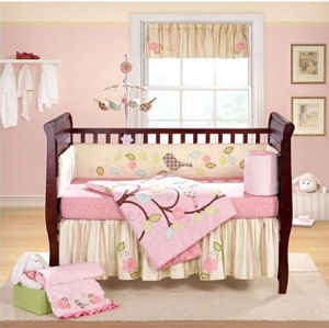 Pink baby bedding crib set for a pink and yellow baby girl nursery with bird mobile applique birds on the quilt and bumper