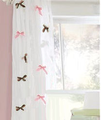 Sheer white curtain panels with pink and chocolate brown bows added to complement a pink and brown baby girl nursery room