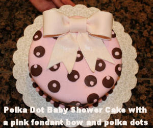 Pink and brown baby shower cake with large fondant bow topper and polka dots for a baby girl