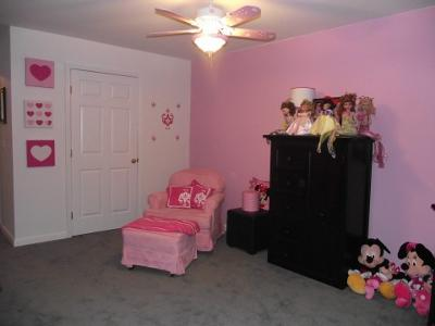 A collection of Disney Mickey and Minnie Mouse dolls and fashion dolls decorate the area to the side of the comfortable pink, upholstered nursery chair and ottoman.