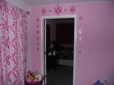 Removable, vinyl Amy Coe wall decals in pink replicate the fabric pattern of the curtain panels and crib set.