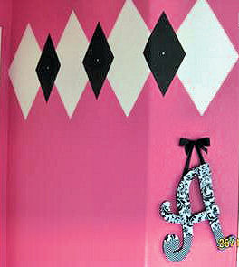 Pink, black and white argyle wall painting technique in a baby girl nursery room