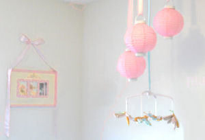 Nursery ceiling mobile made with pink paper lanterns and silk dragonflies hung with satin ribbons