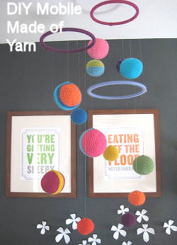 DIY homemade planets theme baby crib mobile for a nursery made of yarn in bright colors