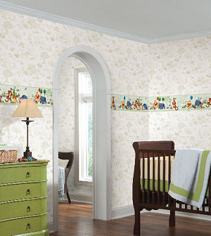 A Winnie the Pooh baby nursery in a sage green and vintage white theme with toile wallpaper