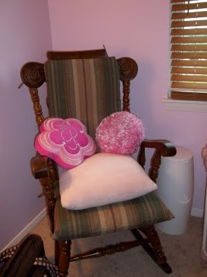 Our baby girl's nursery rocker with brown and pink cushions and throw pillows