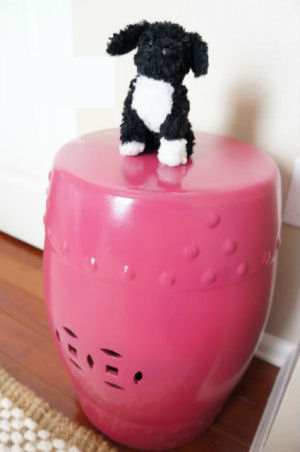 Raspberry pink ceramic garden stool used as decor in a baby girl nursery room