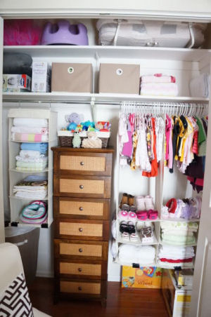 Beautifully organized baby girl nursery closet with shelves cubby holes and drawers