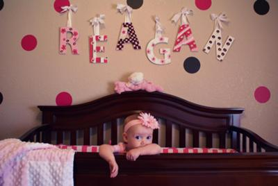 Our baby girl Reagan and her cozy crib!  The wooden letters that spell her name are framed by the pink and brown polka dots that decorate her nursery walls.