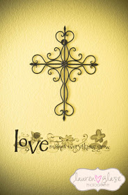 Black iron wall cross with ornate scrollwork and nursery wall decal