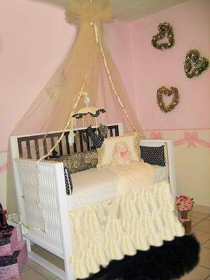 This romantic hearts and roses baby nursery theme room is the picture of femininity with its pastel pink walls and a ruffled crib skirt and canopy.