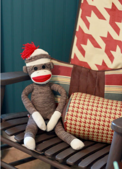 Vintage sock monkey in the rocking chair of a Route 66 themed baby boy's nursery room