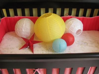 Colorful paper lanterns and stars make super cheap nursery wall and ceiling decorations.  These look amazing with my red gingham baby bedding!