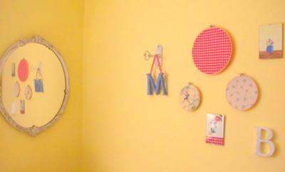 I stretched vintage fabrics in wooden embroidery hoops, painted wooden letters and even an antique door lock and key to make this nursery wall arrangement.