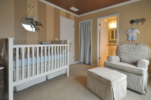 Baby boy nursery with wall stripes painted with taupe color paint and a metallic bronze ceiling
