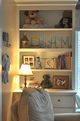 Built in shelves in baby boy nursery filled with gifts and items filled with memories from parents childhood