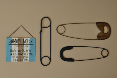 Large bronze baby diaper pins and a personalized verse used as decorations complete the nursery wall decor arrangement