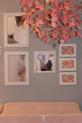 Photos and artwork in a wall display over the baby changing table