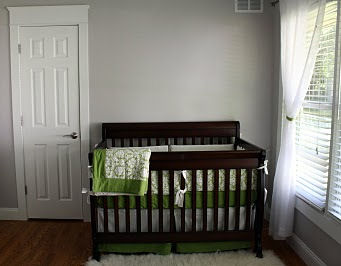 Serene gender neutral nursery design in white, gray and green.