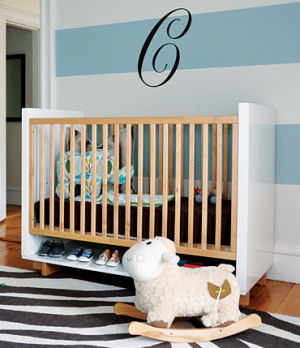 Modern white baby bed with natural wood rails in a blue and white baby boy nursery with a zebra rug