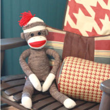 Baby sock monkey nursery theme with rust red and ivory bedding and painted beadboard wall in royal navy blue