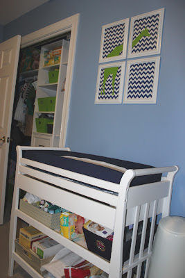 Modern navy blue white and lime green giraffe theme wall art over the changing table in a baby boy nursery