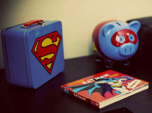Vintage Superman lunchbox, bank and Batman book are decorations for the baby's nursery