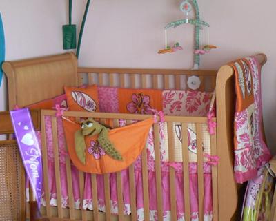 The crib with its pink and orange surf theme baby bedding set that we chose our baby girl's surfer nursery