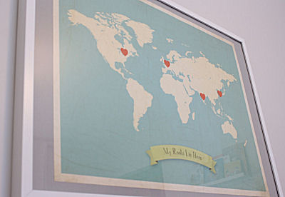 Map artwork on the baby's nursery wall with countries of ancestry marked with hearts