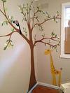 Baby Maddie loves her forest nursery tree wall mural with a colorful toucan and giraffe
