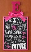 A Bible verse, Jeremiah 29:11 For I know the plans  I have for you, declares the Lord, is framed in fuchsia pink with baby Emerson's initial and a girly bow atop the subway style wall art