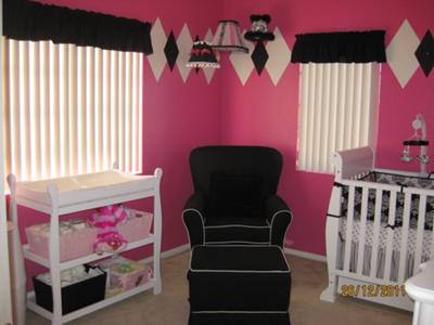 A baby girl nursery room with a painted diamond design pattern on a hot pink color wall