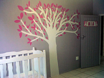Homemade diy painted tree on the wall of a baby girl nursery room