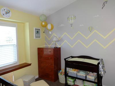 Full view of our baby girl's grey and yellow nursery room and the painted chevron wall stripes that got the entire family involved in the decorating process