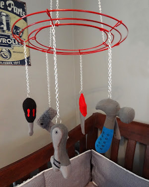 Homemade DIY baby crib mobile hanging with vintage garage tools decorations.