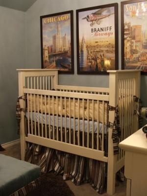 A baby boy nursery room decorated in a vintage travel theme with antique framed transportation posters