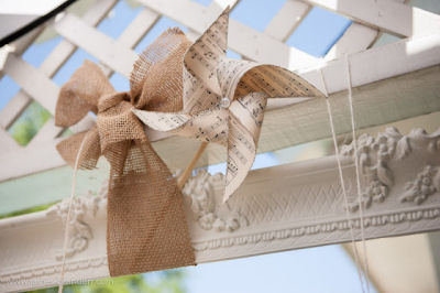 Homemade pinwheels made from vintage sheet music decorated with rustic burlap bows