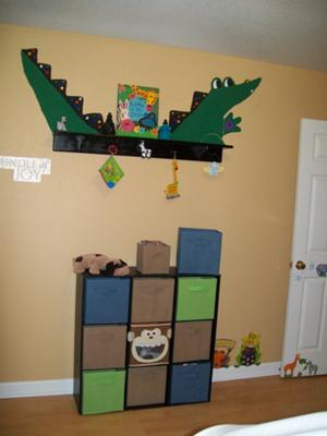 The large green alligator is painted on a solid beige color wall in a baby boy's nursery transforming a plain wall shelf into something spectacular!