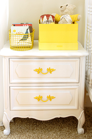 Vintage DIY night stand makeover before and after pictures painted white with yellow drawer pulls for a baby nursery