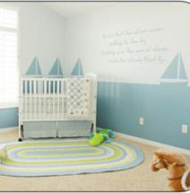 A sailboat nursery with a wall mural painting for a baby boy