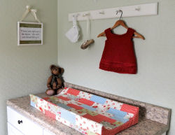 Vintage baby shoes and handknit sweater above the changing table.  The changing pad's cover matches the crib quilt made from Moda's 3 Sisters Glacé fabrics.