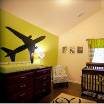 Green and black airplane theme nursery with damask crib bedding