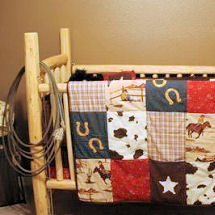 Homemade rustic western theme log baby crib with patchwork baby nursery bedding.