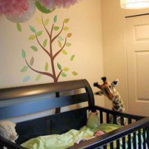 Pink and green baby giraffe theme nursery with tissue paper pom poms crib mobile and giant plush giraffe toy and tree wall mural with leaves