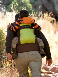 Baby in the Boba Organic Baby Carrier in back carry position hiking with dad.