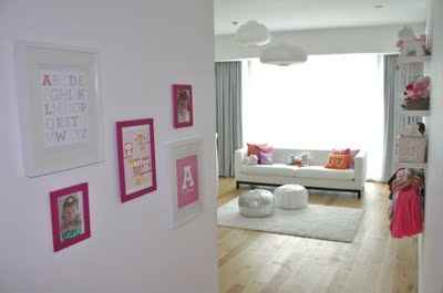 Personalized baby nursery wall art in magenta and white picture frames in an attractive arrangement