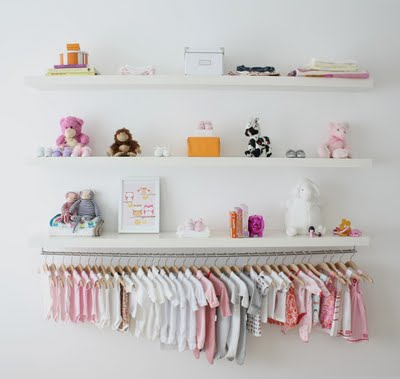 A wall display of wooden shelves with decorations and baby girl outfits organized on matched hangers according to size