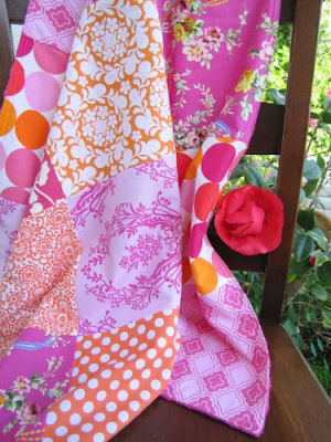 Minky Patchwork baby quilt featuring various shades of pink lavender and orange in floral and polka dots fabric