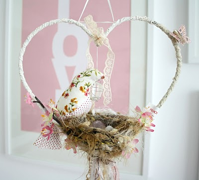A dreamcatcher/baby crib mobile with fabric birds in a nest supported by a heart shape frame decorated with butterflies
