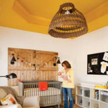 Rustic neutral farm theme baby nursery with barn board features and mustard yellow tray ceiling